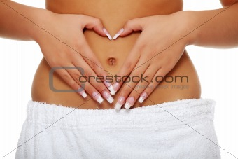 Woman making heart shape on her belly