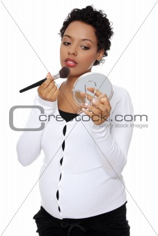 Pregnant woman doing a make up.