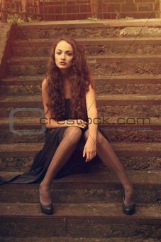 Beautiful fashion girl sitting on the stairs