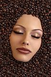 girl&#39;s face immersed in coffee beans 