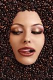 close up portrait of a girl&#39;s face immersed in coffee beans