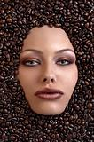 pretty girl's face immersed in coffee beans