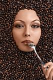 face shot of a beautiful girl immersed in coffee beans