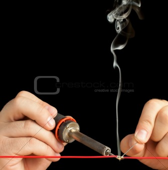 Technician bonding two wires with a solder joint.