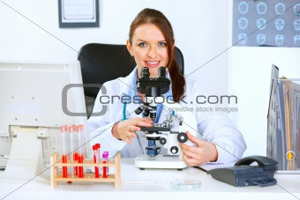 Smiling doctor woman using microscope in laboratory
