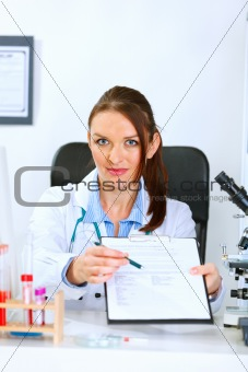 Doctor woman sitting at office table with document and pen for signing