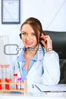 Smiling doctor woman with headset sitting at office table