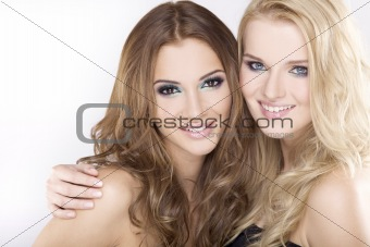 Two smiling girl friends - blond and brunette
