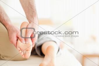 Male masseur massaging a woman's feet