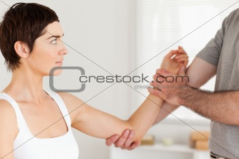 Chiropractor examining a woman's arm