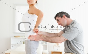 Chiropractor examining a cute woman's back