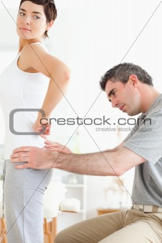 Chiropractor examining a brunette woman's back