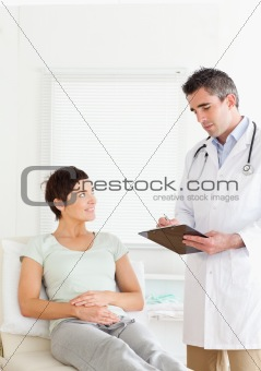 Woman lying down talking to a doctor