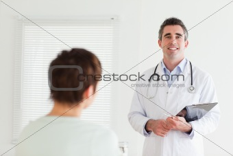 Smiling Doctor talking to a brunette woman