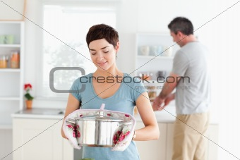Cute Woman holding a pot while man is washing the dishes