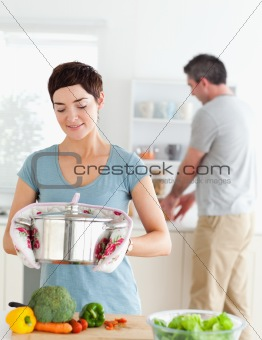 Cute wife holding a pot while her husband is washing the dishes