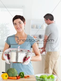 Charming wife holding a pot while her husband is washing the dishes