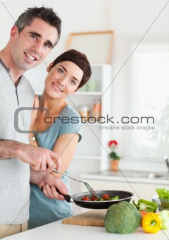 Gorgeous Woman and her pan-holding husband looking into the camera