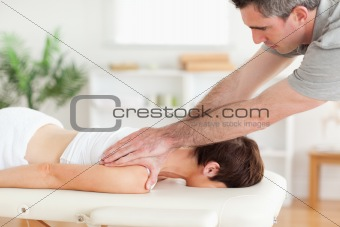 A masseur massaging customer's neck