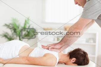 Masseur massaging female customer's back