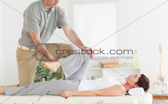 Chiropractor stretches woman's arm