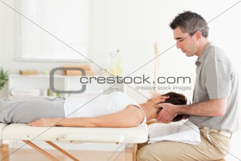 Masseur stretching woman's head