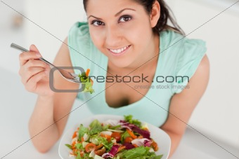 Cute young woman eating salad