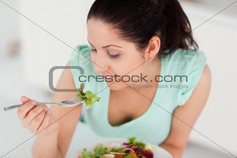 Beautiful young woman eating salad