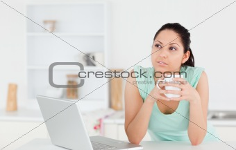 Thoughtful young woman with laptop and coffee