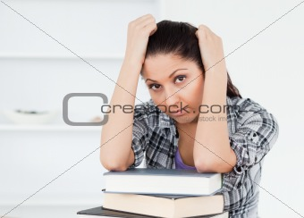 Tired young student resting on books
