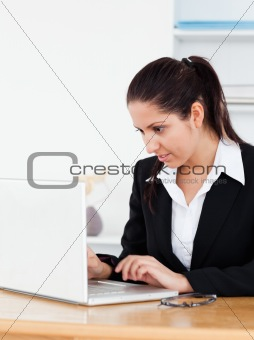 Young businesswoman with laptop in office