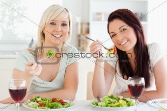 Cheerful young Women eating salad