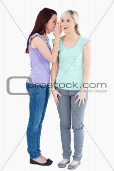 Charming woman telling friend a secret