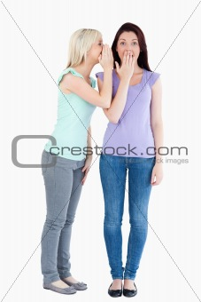 Charming woman telling her friend a secret