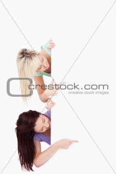 Charming Women peeking around a banner showing copyspace