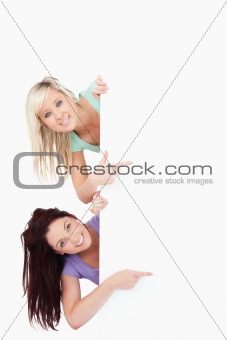 Cute Women peeking around a banner showing copyspace