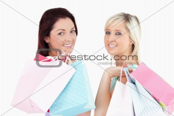 Cute young women with shopping bags