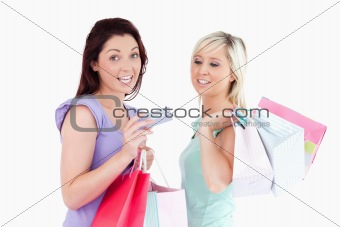 Charming women with shopping bags and a card