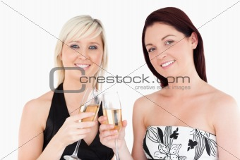 Cute women in beautiful dresses toasting with champaign