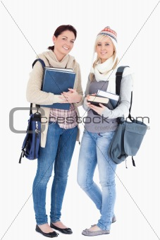 Two students with books prepared for winter