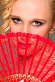 Portrait of girl closing face with textile fan