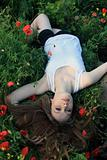 Passionate girl lying on the poppies