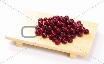 Bowl with ripe cherries. Isolated on a white background.