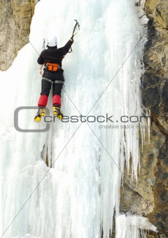 Young man, ice climbing an attractive route.