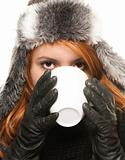 young woman in winter dress drinking coffee or tea from a cup