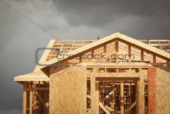 Home Construction Framing with Ominous Grey Clouds Behind.