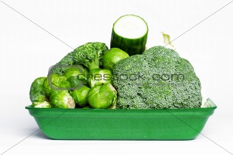 Green tray with vegetables on white