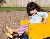 Little girl smiling and sliding on children&#39;s chute