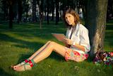 A Young Woman Uses Tablet PC In The Park