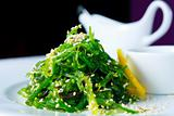 Chuka seaweed salad garnished with sesame seeds and lemon